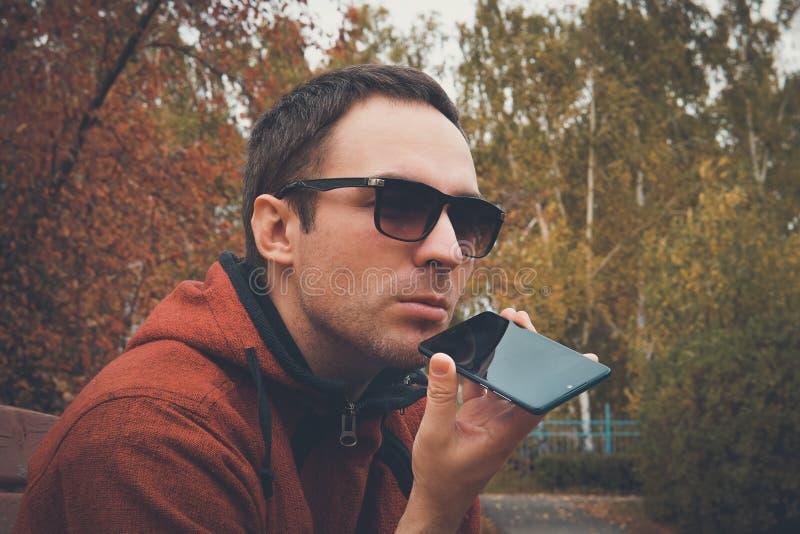 年轻帅哥身分在公园在夏天,使用手机听记录的语音留言或音频 ? 库存照片