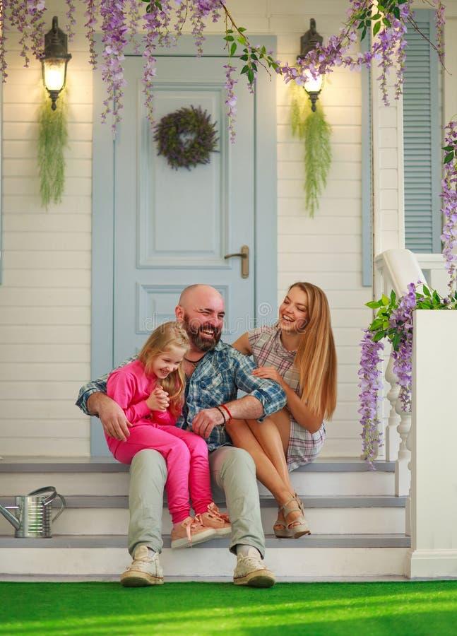 年轻幸福家庭获得乐趣在避暑别墅的庭院 免版税库存照片