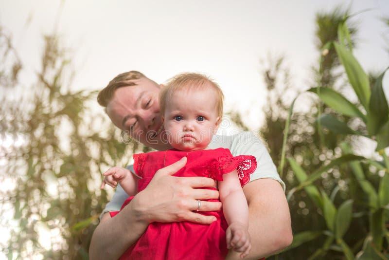 年轻幸福家庭走室外 父亲在手上的举行孩子和高兴 免版税库存图片
