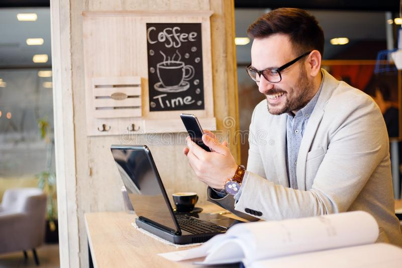 年轻建筑师在咖啡馆看建筑计划时用手机 免版税库存照片
