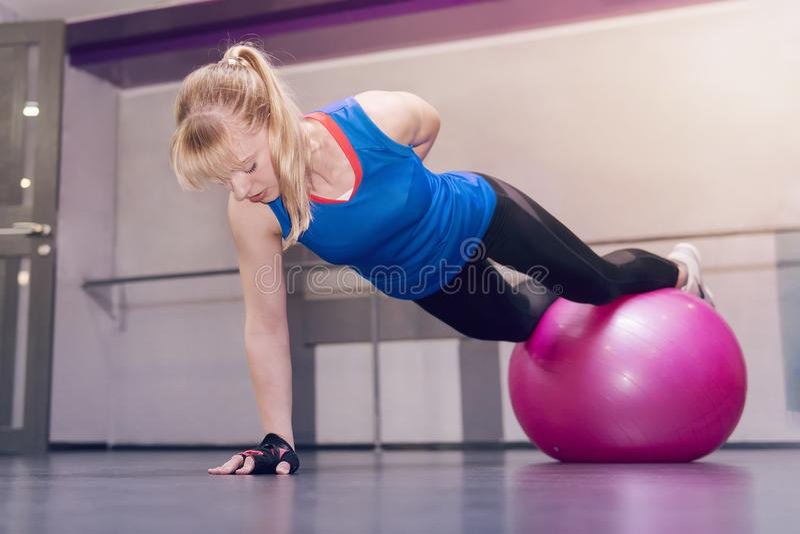 年轻式样女孩做锻炼在健身房 一方面立场 有吸引力的白肤金发的与fitball的健身式样执行的俯卧撑, 免版税库存照片