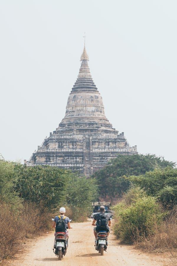 年轻往古老蒲甘Shwesandaw塔的夫妇骑马电滑行车在缅甸 免版税库存图片