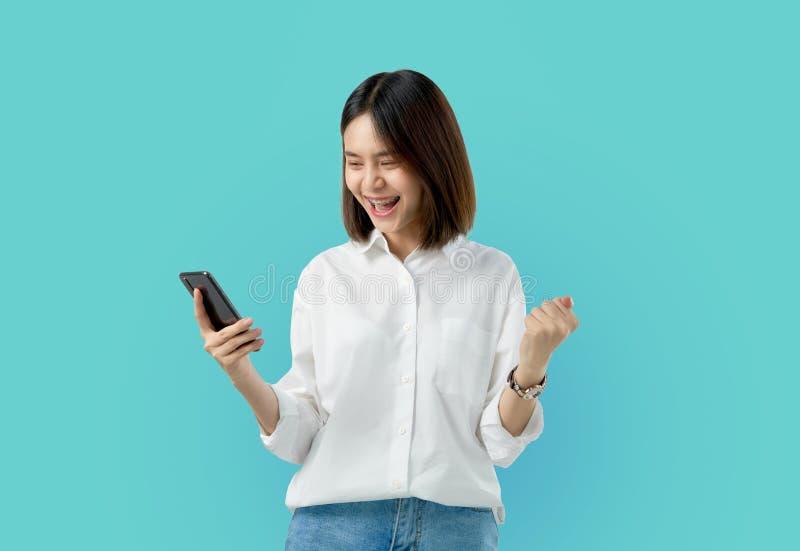年轻微笑的亚洲妇女藏品智能手机用拳头手和激发为在浅兰的背景的成功 库存图片
