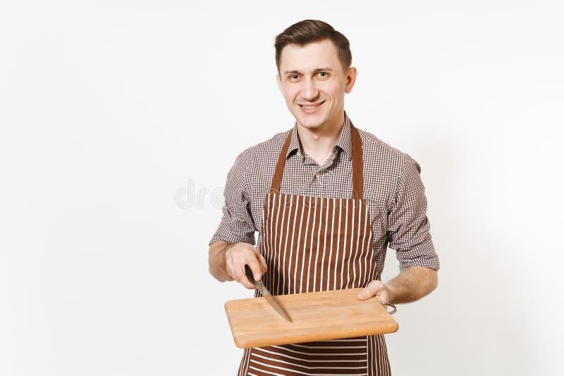 年轻微笑的人厨师或侍者镶边棕色围裙的,拿着木切板,刀子的衬衣隔绝在白色 免版税库存图片