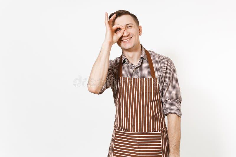 年轻微笑的人厨师或侍者镶边棕色围裙的,衬衣陈列OK姿态在白色背景隔绝的眼睛 免版税库存图片