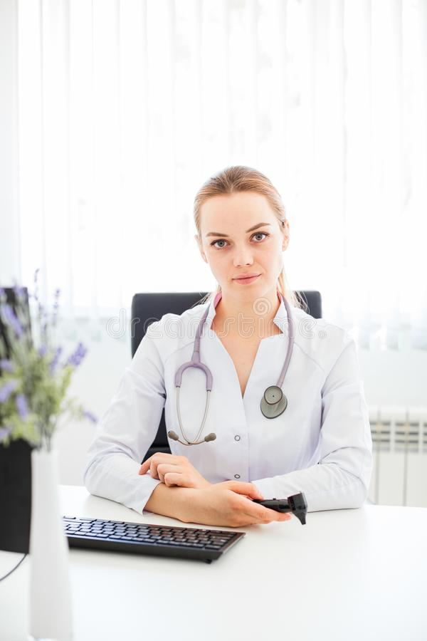 年轻微笑的医生在书桌坐与她的胳膊的一把黑椅子横渡了 库存图片