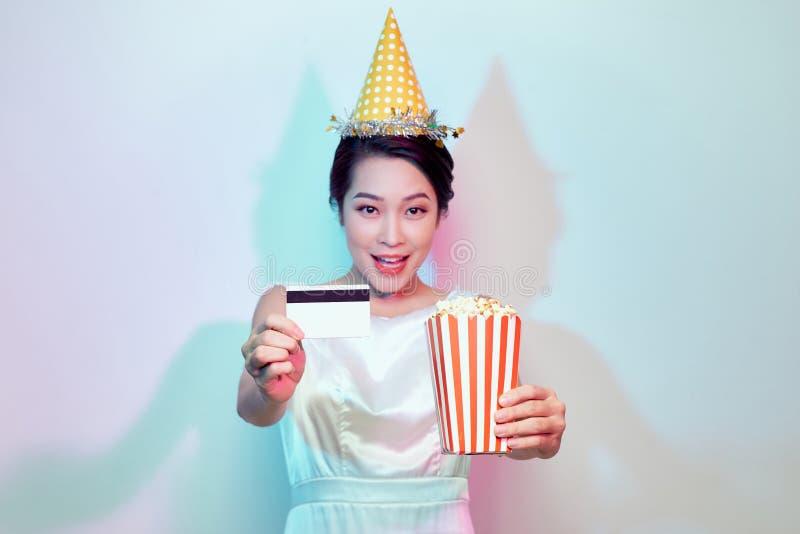 年轻微笑的可爱的深色的妇女画象便服电影影片的,拿着桶玉米花和信用 库存图片