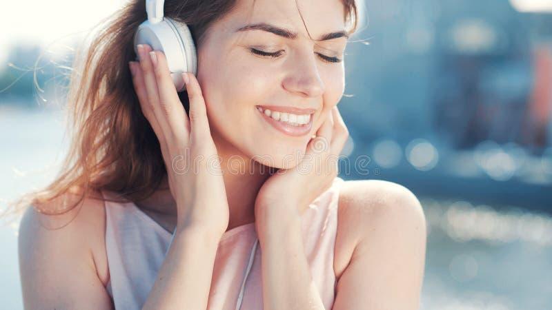 年轻微笑的女孩听到音乐 免版税库存图片