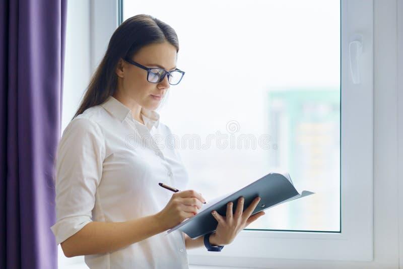 年轻微笑的女实业家画象在办公室,女性在拿着文件的玻璃在窗口附近 库存图片