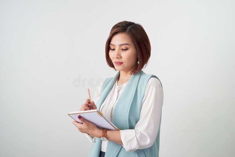 年轻微笑的女实业家画象在办公室,拿着在轻的背景的文件 免版税库存照片