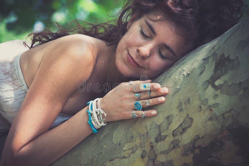 年轻微笑的妇女大自然爱好者在夏日拥抱享用树 免版税库存照片