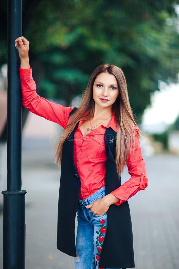 年轻微笑的妇女画象看照相机的一件红色衬衣和一件长的无袖的夹克的 站立在s的愉快的白肤金发的女孩 免版税库存照片