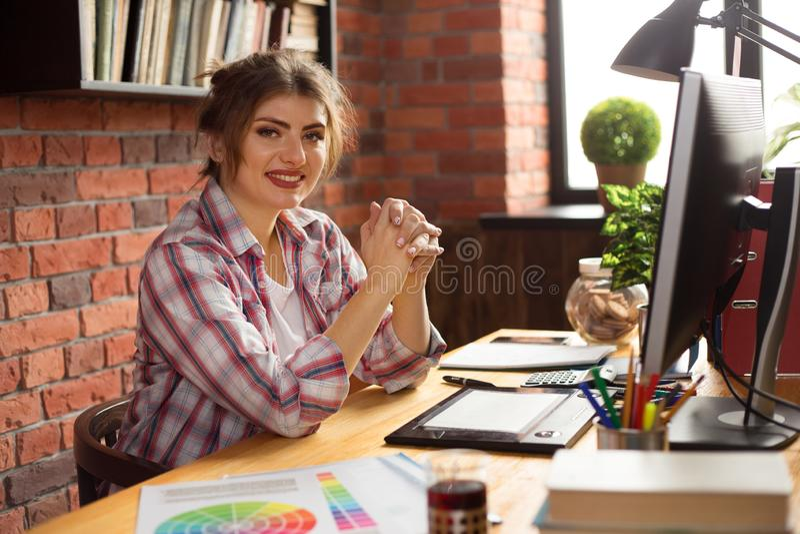 年轻微笑的妇女设计师或照片编辑程序在运作在计算机和图形输入板上的办公室 库存例证