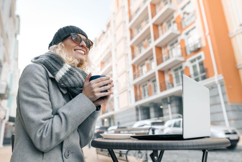 年轻微笑的妇女,被编织的帽子画象衣服暖和的 温暖她的有杯子的女孩手在一个室外咖啡馆的热的饮料  免版税库存图片