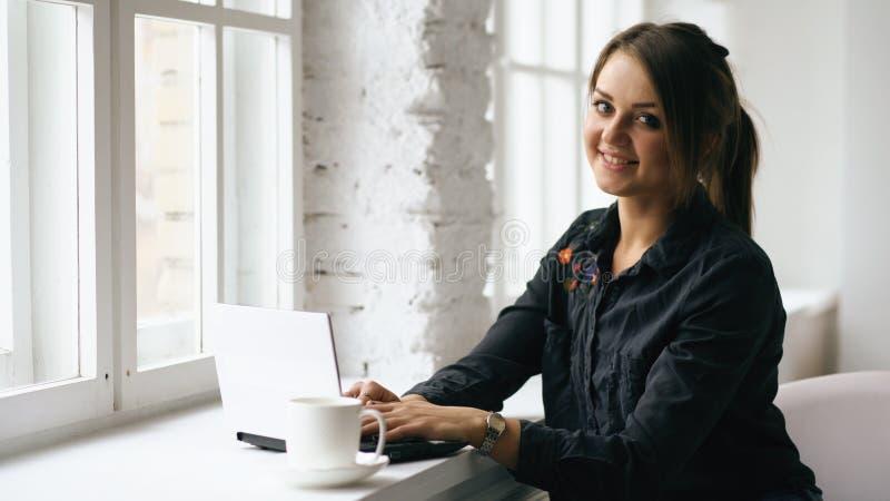 年轻微笑的学生妇女在咖啡店坐在与膝上型计算机的桌上户内 免版税库存图片