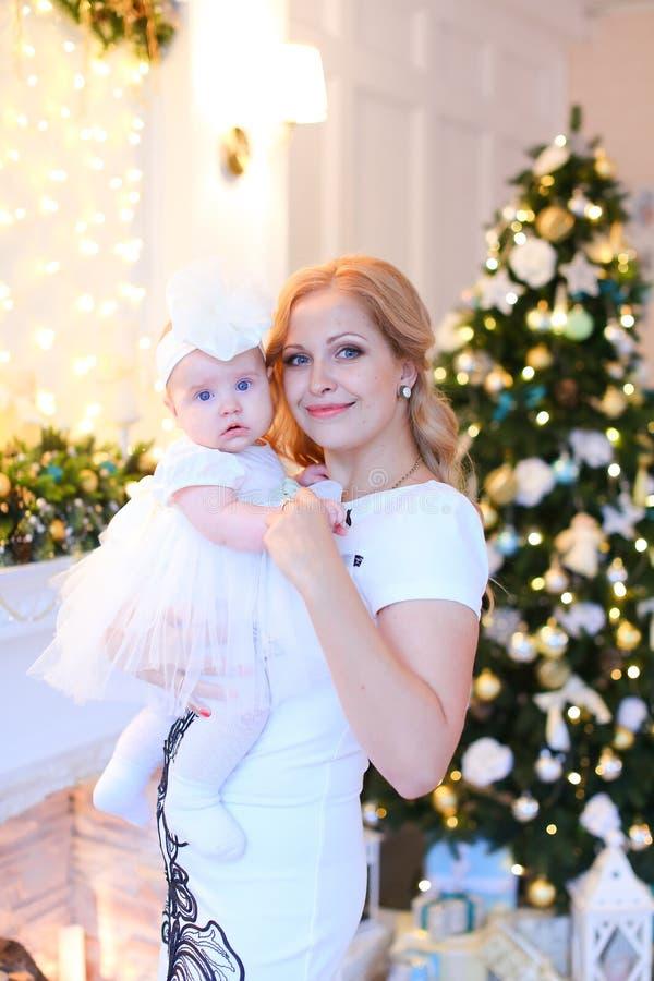 年轻微笑的母亲佩带的白色礼服和保留在圣诞树附近的小女性婴孩 库存图片