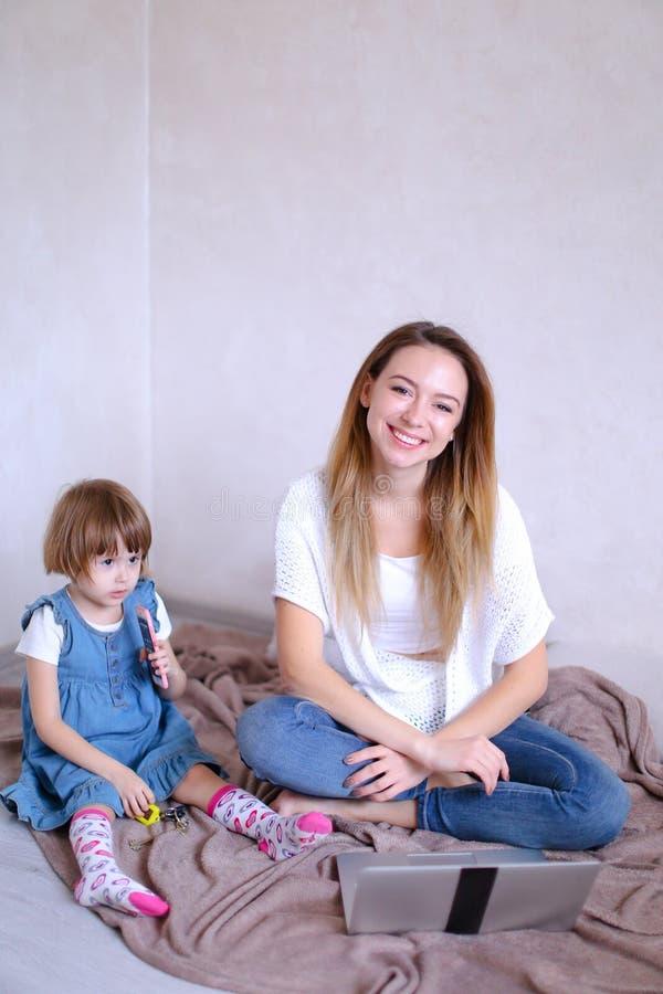 年轻微笑的母亲坐与小女儿的床在膝上型计算机附近 免版税库存照片
