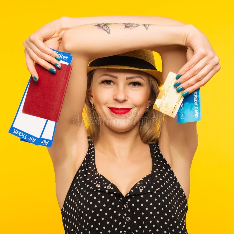 年轻微笑的激动的女学生藏品护照登机牌票和在黄色背景隔绝的信用卡 免版税库存照片