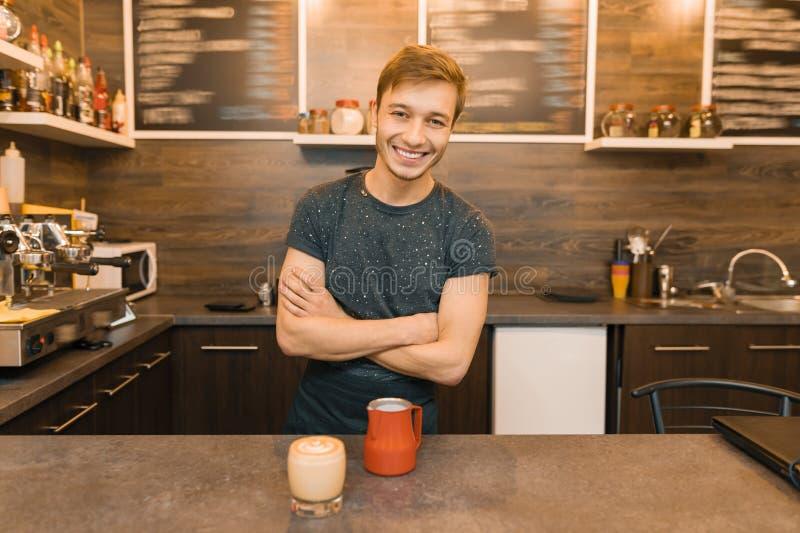 年轻微笑的男性咖啡馆工作者画象,站立在柜台 人用被折叠的手用新近地做的咖啡 库存照片