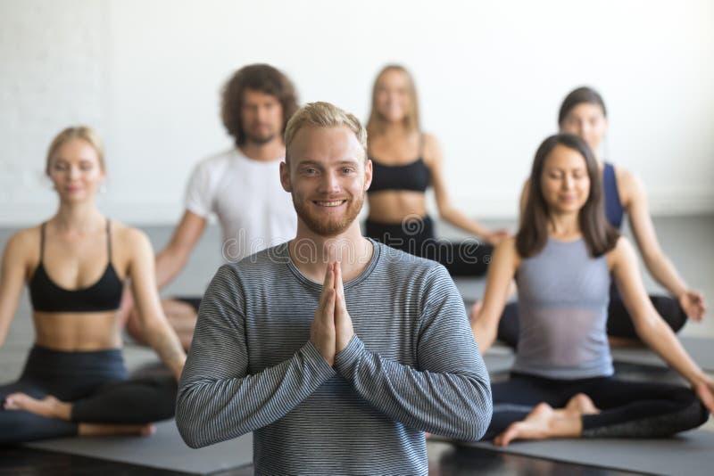 年轻微笑的男性瑜伽辅导员和小组在莲花摆在 免版税图库摄影