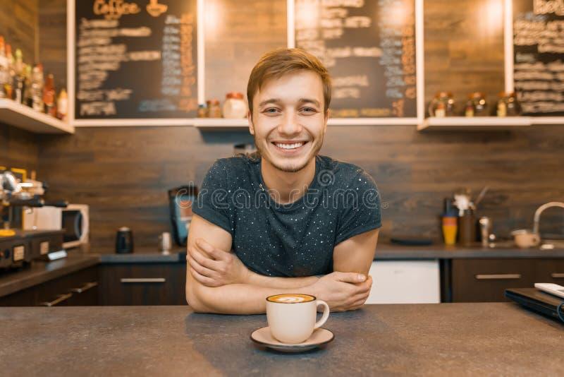 年轻微笑的男性barista画象与准备的饮料的与胳膊横渡了站立在咖啡馆柜台后 咖啡馆事务co 免版税库存图片