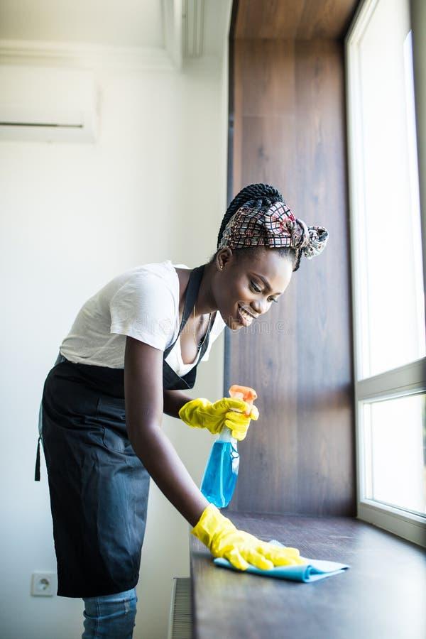 年轻微笑的美国黑人的妇女的画象洗涤与旧布和风窗清洁器的黄色手套的窗台户内 免版税库存照片