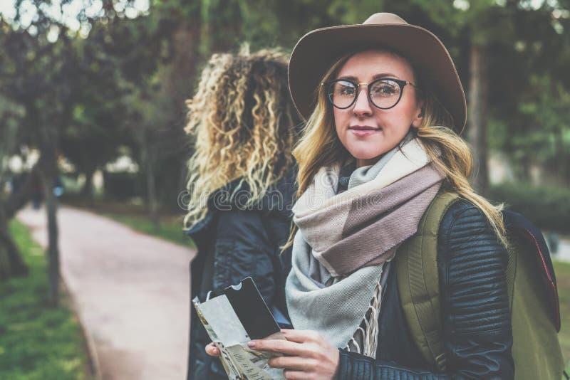 年轻快乐的妇女游人画象帽子的,玻璃和有背包的,站立室外和拿着目的地地图 免版税库存图片