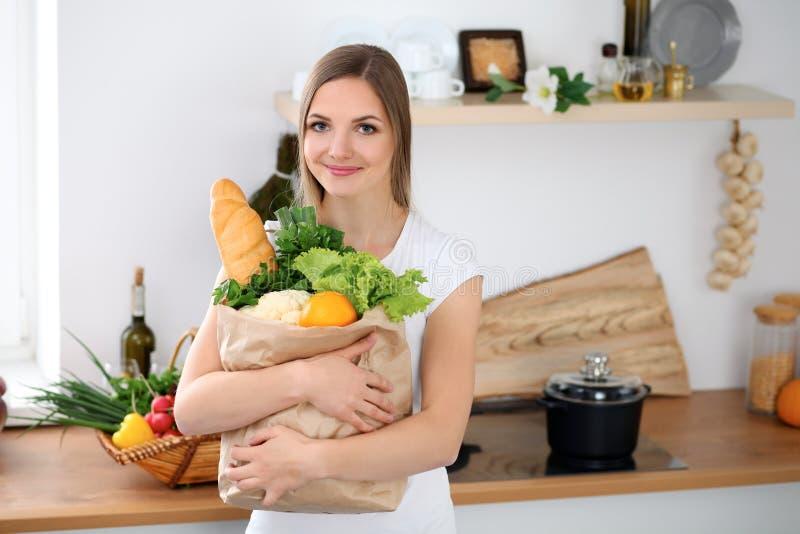 年轻快乐的微笑的妇女准备好烹调在厨房里 主妇拿着大纸袋有很多新鲜 库存图片