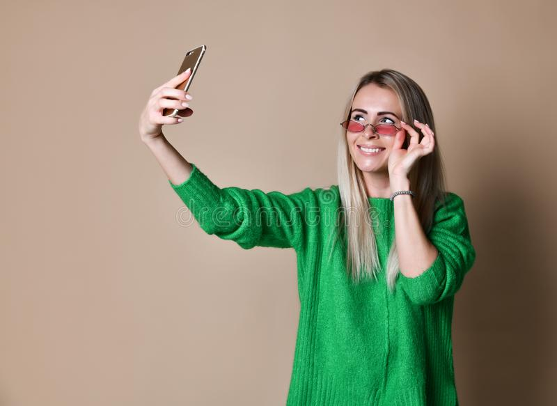 年轻快乐的毛线衣穿戴的时尚白肤金发的妇女特写镜头画象在智能手机做selfie,在米黄背景 图库摄影