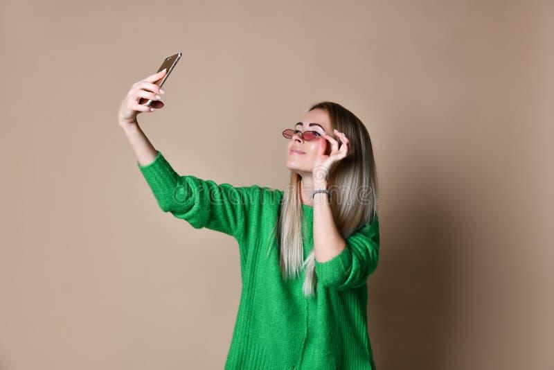 年轻快乐的毛线衣穿戴的时尚白肤金发的妇女特写镜头画象在智能手机做selfie,在米黄背景 库存图片