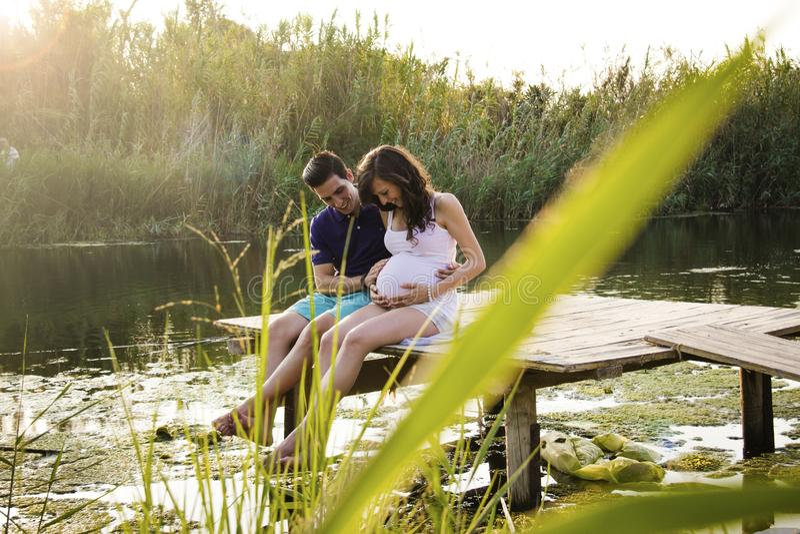 年轻怀孕的夫妇坐木平台 免版税图库摄影