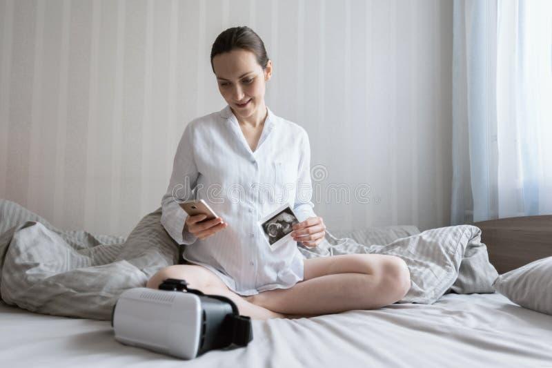年轻怀孕的白种人妇女坐与智能手机和超声波图片和vr玻璃的床 库存照片
