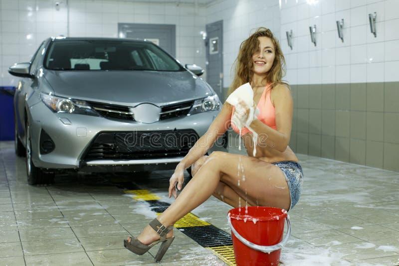 年轻性感的妇女洗涤汽车 免版税库存照片