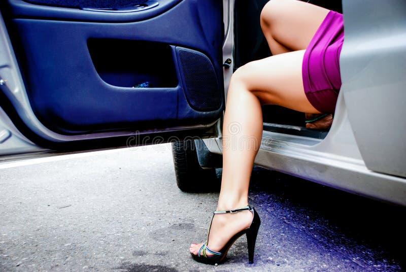 年轻性感的妇女离开汽车 库存照片