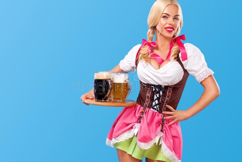 年轻性感的慕尼黑啤酒节女孩-女服务员,穿一件传统巴法力亚礼服,在蓝色背景的服务的大啤酒杯 免版税库存图片