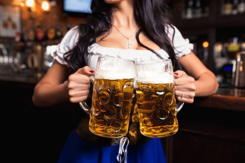年轻性感的慕尼黑啤酒节女服务员,穿一件传统巴法力亚礼服,服务的大啤酒杯在酒吧 免版税库存图片