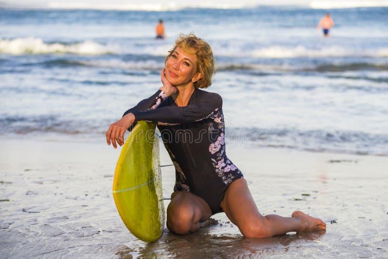 年轻性感的美丽和愉快的冲浪者妇女坐拿着黄色水橇板微笑的快乐的享用的夏天holid的海滩沙子 免版税库存照片