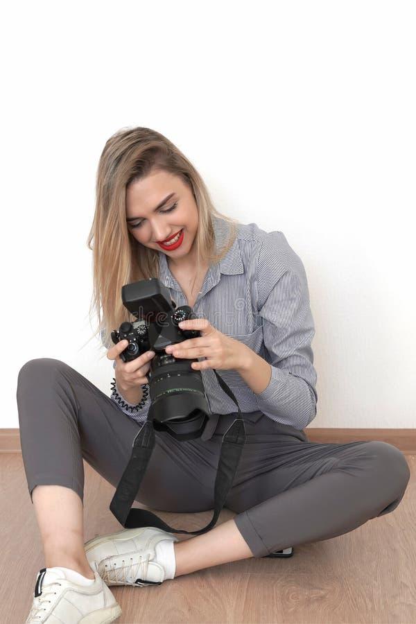 年轻性感的金发碧眼的女人坐地板在演播室并且观看在照相机的英尺长度 免版税库存图片