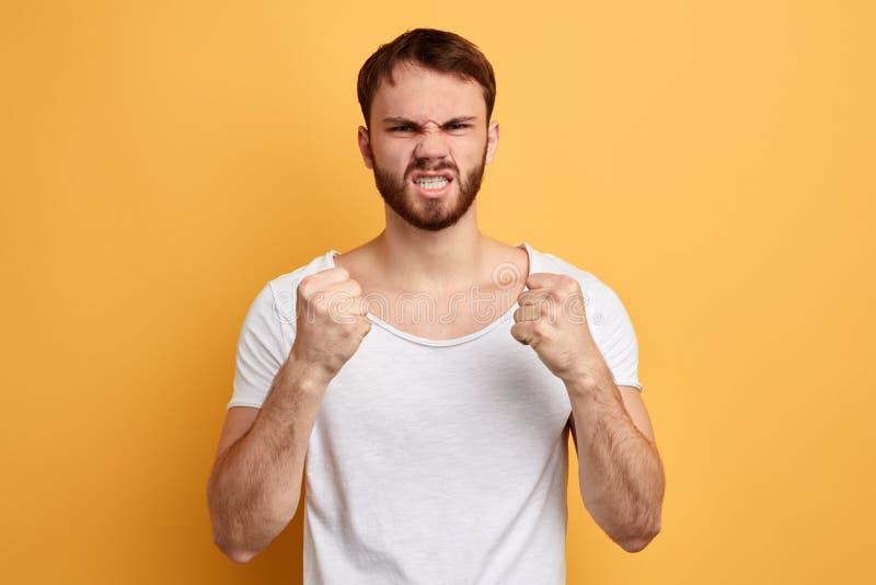 年轻恼怒的残暴的人紧握拳头和呼喊 免版税图库摄影