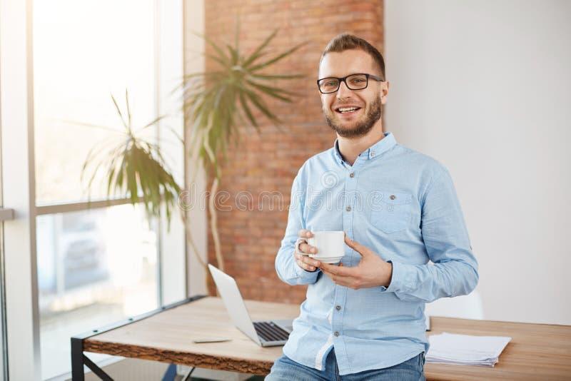 年轻悦目有胡子的企业家画象玻璃和便衣的,站立在明亮的coworking的办公室 图库摄影