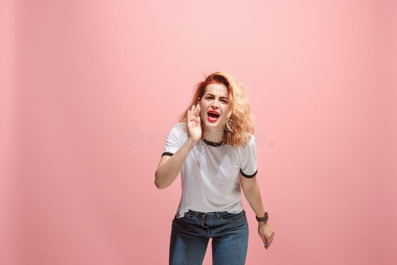年轻情感恼怒的妇女尖叫在桃红色演播室背景 图库摄影