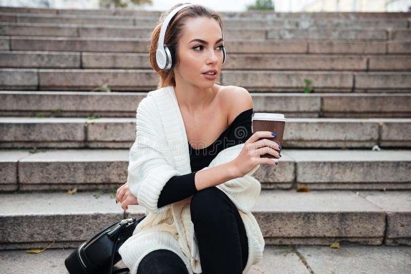 年轻惊人的妇女坐喝咖啡的步 在旁边查找 库存照片