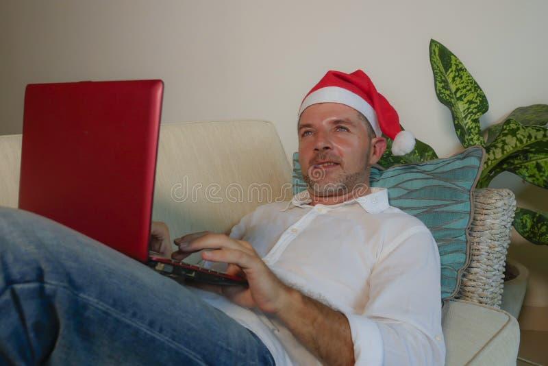 年轻愉快和可爱的人在使用信用卡的圣诞老人克劳斯买的网上圣诞礼物和g帽子和手提电脑 图库摄影