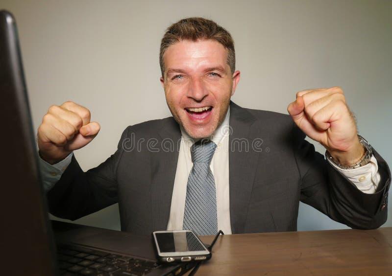 年轻愉快和可爱的商人与手机一起使用在庆祝成功打手势的办公计算机书桌激动  库存图片