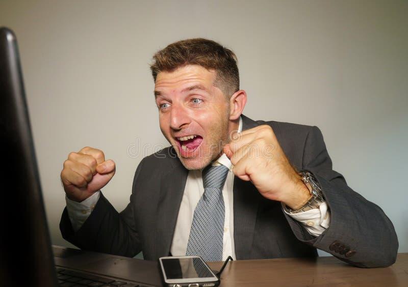 年轻愉快和可爱的商人与手机一起使用在庆祝成功打手势的办公计算机书桌激动  库存照片