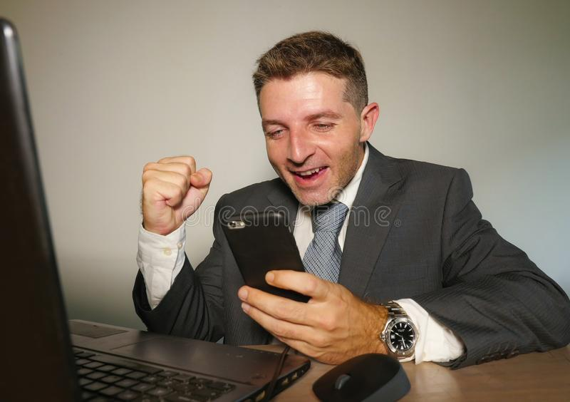 年轻愉快和可爱的商人与手机一起使用在庆祝成功打手势的办公计算机书桌激动  免版税图库摄影