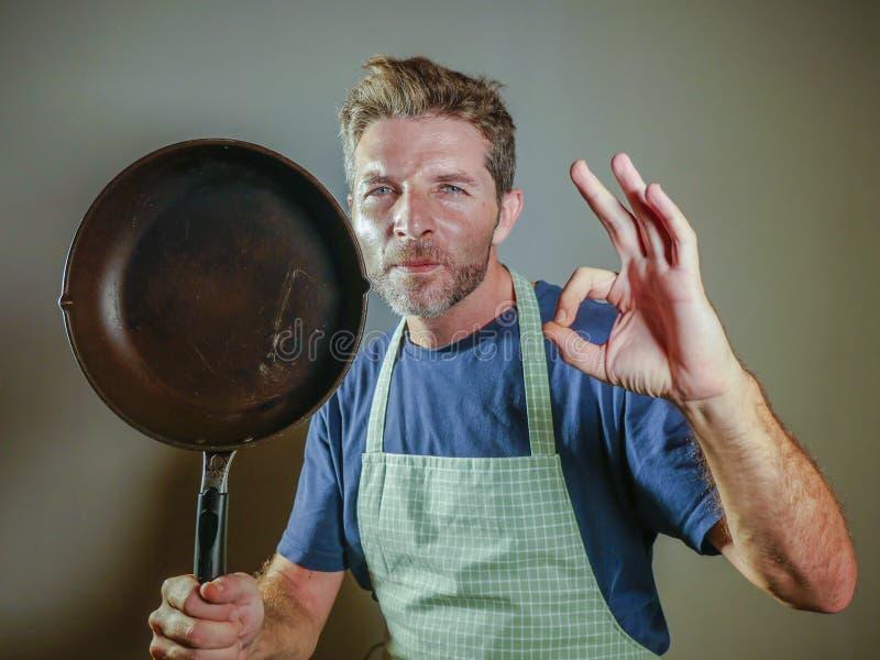 年轻愉快和可爱的家庭厨师人对负烹调微笑的满意的平底锅在被隔绝的背景的和骄傲的给的好标志 库存图片