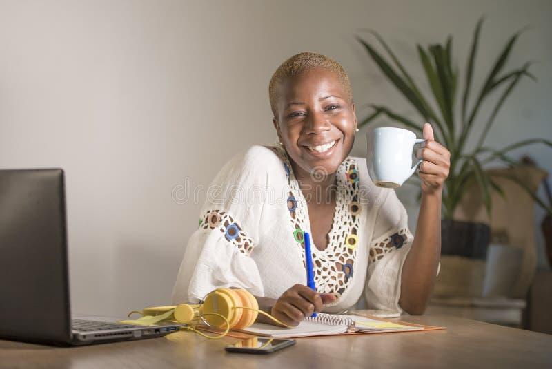 年轻愉快和可爱的行家黑色美国黑人的妇女饮用的茶或咖啡在家办公室工作快乐与膝上型计算机co 免版税库存图片