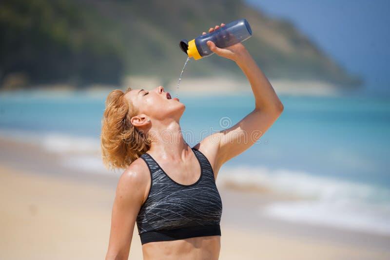 年轻愉快和有吸引力的体育赛跑者妇女饮用水瓶或能量饮料在连续锻炼以后在热带天堂b 库存照片