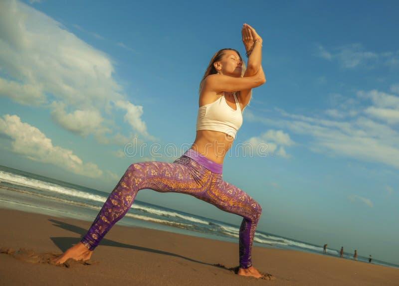 年轻愉快和有吸引力的做户外瑜伽和放松锻炼的适合和皮包骨头的白肤金发的妇女在美丽的海滩放松和 库存照片